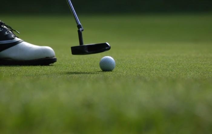 man putt golf ball green